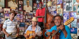 Four Caribbean playing musical instruments.
